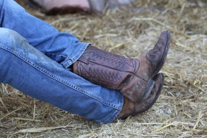 Cowboy with leather boots and a pair of jeans in the stable of the ranch