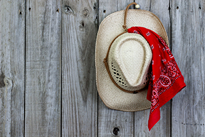 Cowboy hat with bandanna hanging on rustic background